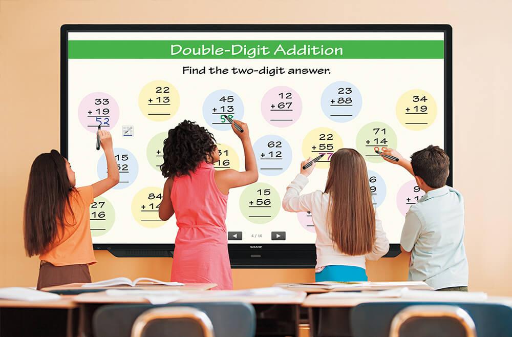 Alumnos hacen sumas en el monitor de la clase