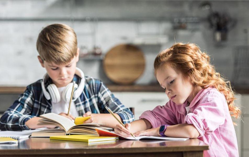 Niños haciendo deberes en la cocina